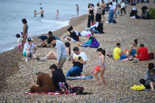 People enjoy the warm weather on Brighton Beach on Sunday. Britain's 27C (81F) Indian Summer will be blasted away by a 65mph 800 mile-wide storm and a 'polar plume' threatening one of England's earliest snowfalls for a century
