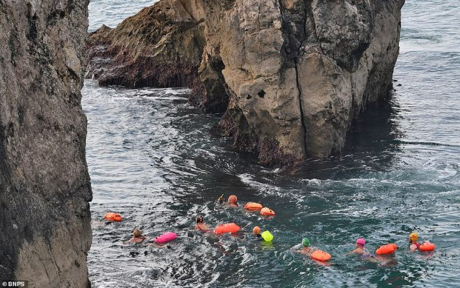 Colourful swimmers make their way through the Durdle Door arch on Sunday afternoon. Daytrippers clogged up coastal routes including the A23 to Brighton, A31 to Dorset and A30 to Cornwall