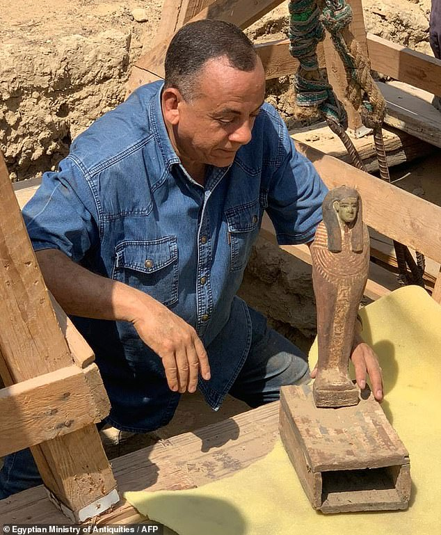 The Egyptian Secretary General of the Supreme Council of Antiquities, Mostafa Waziri, carries one of the sculptures found next to the sarcophagi outside the excavation site