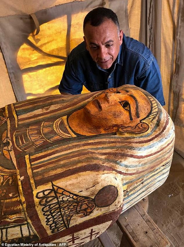 27 sarcophagi that were buried 2,500 years ago have been discovered in the ancient necropolis of Saqqara near Cairo.  Pictured: Egyptian Secretary General of the Supreme Council of Antiquities Mostafa Waziri inspects one of the coffins