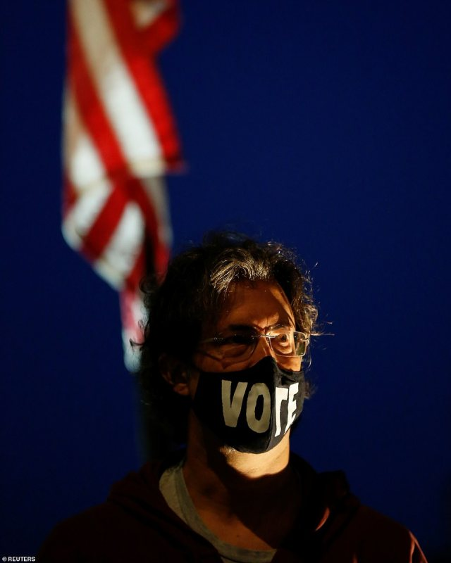 MAINE: One mourner wears a face mask with the word 'vote' across it as thousands come out across America to pay their respects to the late judge