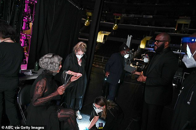 Backstage, Tyler - who's well known for his frequent charitable acts - chatted with presenter Laverne Cox (2-L) as crew members wearing masks stood by between segments