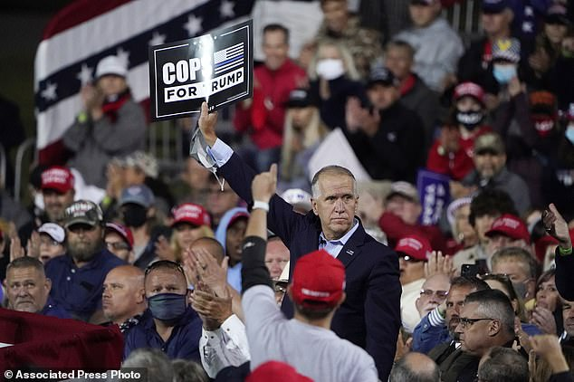 GOP Sen. Tom Tillis (center) holds a sign as President Donald Trump speaks at a campaign rally, Saturday, September 19 in Fayetteville, North Carolina