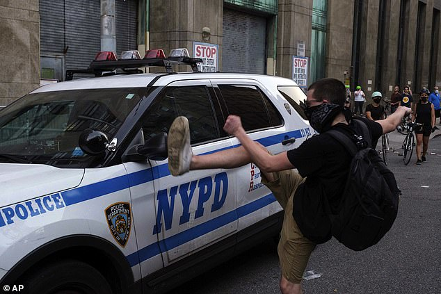 "A protester kicks a police vehicle in an attempt to break its side mirror during a ""Solidarity with Portland"" protest Saturday, July 25, 2020, in New York. The memo faults DAs in the city for failing to prosecute disorderly conduct"
