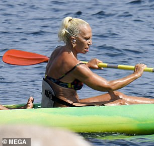Stylish: Donatella pulled her blonde locks back into a tight ponytail, and she chose to wear smokey eye shadow and nude lipstick for the outing by the sea