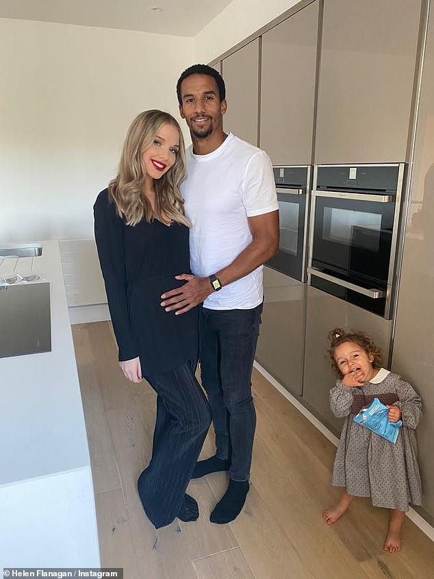Family: Helen looked gorgeous in a tight black jumper showing off her bump teamed with ruby red lipstick as she happily posed with Scott and their daughters