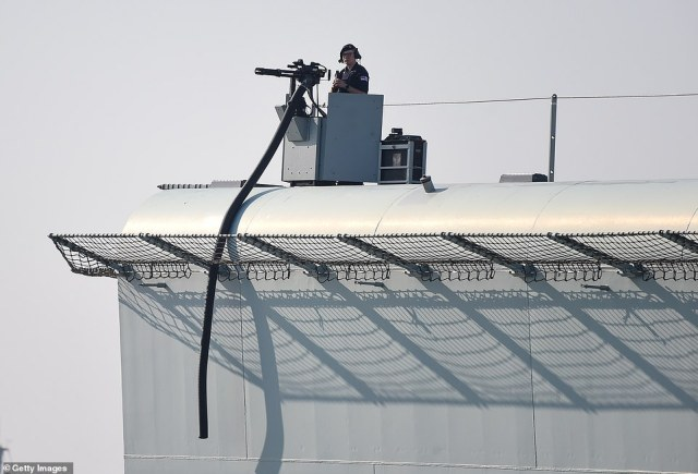 The 900ft titan, one of two newly built carriers, was hauled out of the harbour by six super-powered tugs as hundreds lined the coast to watch her go (pictured: a machine gunner stands in his nest)