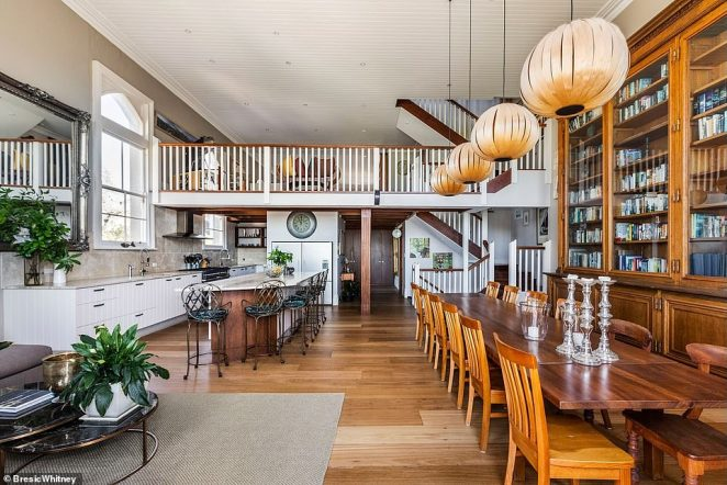 The kitchen-cum-dining area is fitted with floor-to-ceiling bookcases, custom timber cabinets and Italian marble