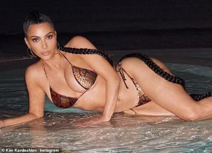 Foto lista: Kim usó aretes de aro de plata deformados y lucía una extensión de trenza hasta el cuerpo a la moda en los sexy broches