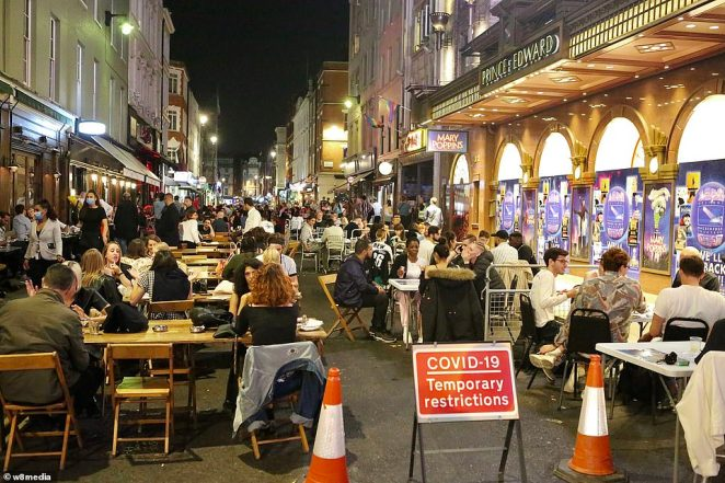 Exasperated hospitality sector bosses are crying out for clarity over whether the 10pm curfew is the point they must clear the premises, which is feared would slash revenues by 50 per cent and cause a jobs bloodbath (Pictured: Soho in London last night)