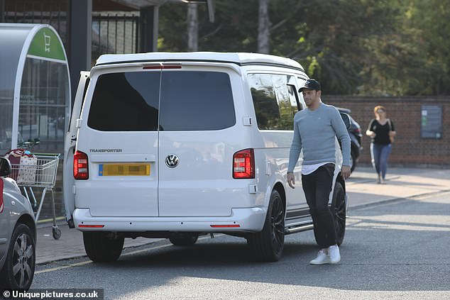 Laid back:Joe also opted for a casual look, wearing a grey jumper with black skinny jeans and a matching cap