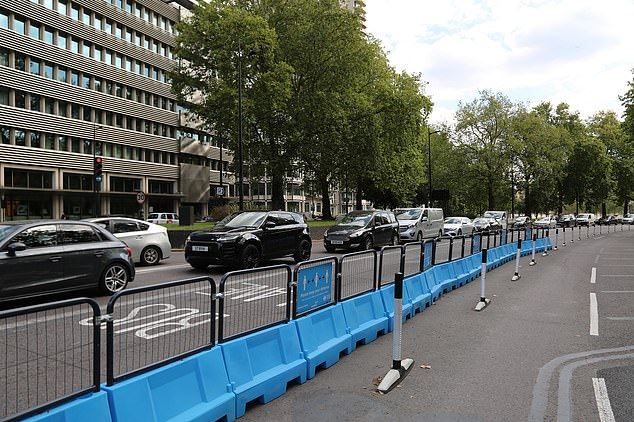 Cars queue next to an empty cycle lane on Park Lane in London's Mayfair district at 2.30pm