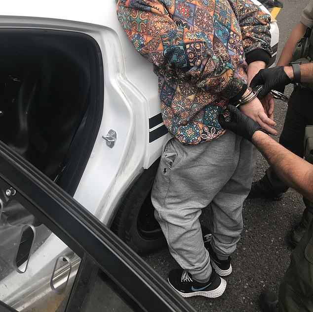 Justin Valente, 32, being placed under arrest after a highway chase