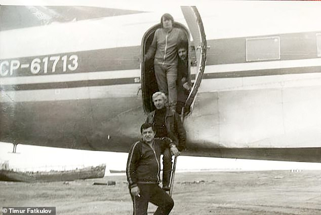 The crew stands on the steps of the CCCP-6173 during its heyday in the Soviet Union before it was abandoned in the Siberian plane graveyard