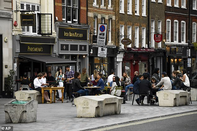 People enjoy a socially-distanced pint at a pub on the outskirts of Covent Garden, London