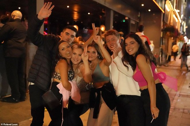 Revellers are set to descend on pubs and bars for a final evening of late-night drinking before Boris Johnson's new Covid curfew kicks in tomorrow. Pictured: Revelers leaving a student bar in Birmingham last night