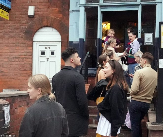 People queue outside The Bristol Pear pub just hours after the Government toughened its coronavirus measures