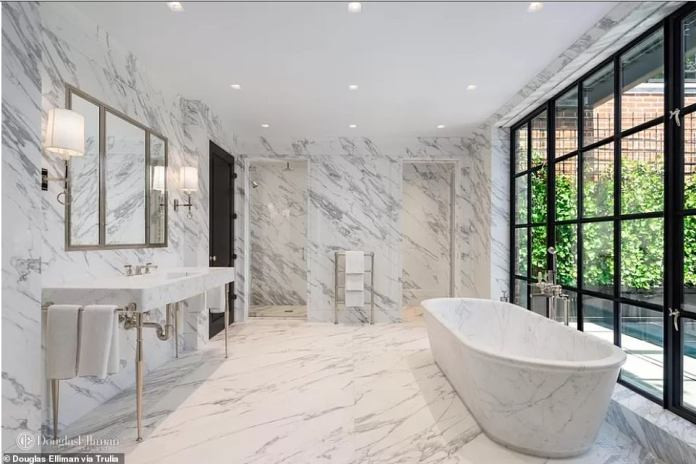 The master bathroom features two showers, a soaking tub and plenty of Italian marble