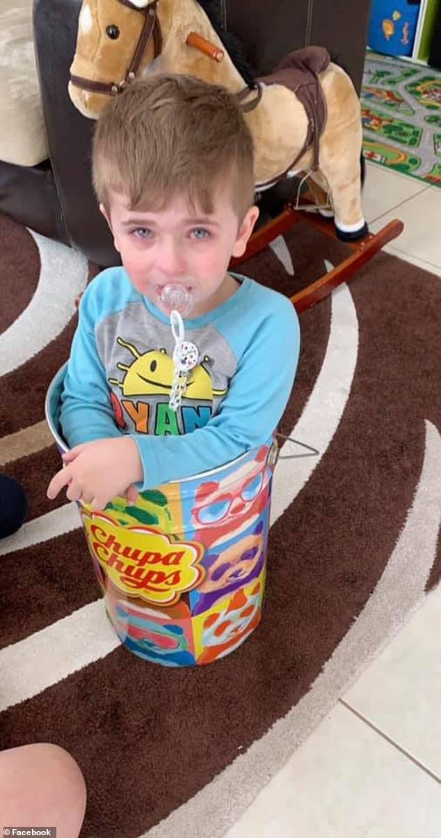 Alessio Caruso had been playing in the large lollie tin at his home in Melbourne on Wednesday when he became wedged in the small space