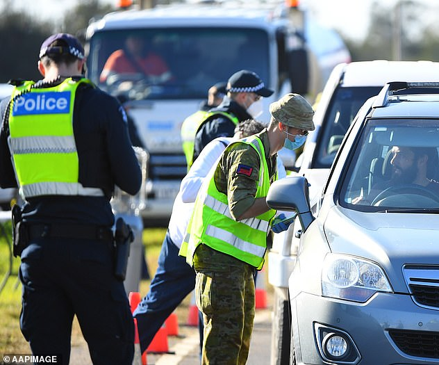 Pictured are ADF personnel manning a Princes Highway checkpoint outside Melbourne