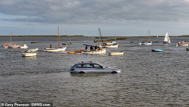 Bizarre photos show bemused sailors cruising past the near-drowned silver car, which appears to have its front, driver-side window left open as the water rose around it