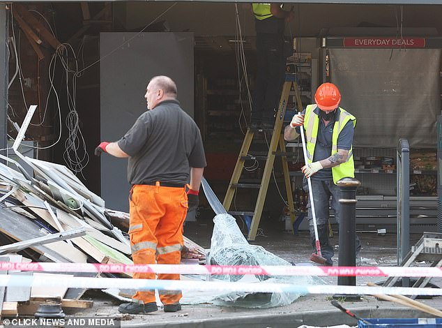 Workmen clearing up the remains of the shattered shopfront after the Co-op raid on Sunday