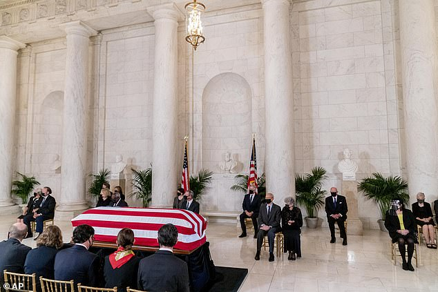 The Supreme Court justices and their spouses sit in front of the flag-draped casket of Justice Ruth Bader Ginsburg during Wednesday's ceremony