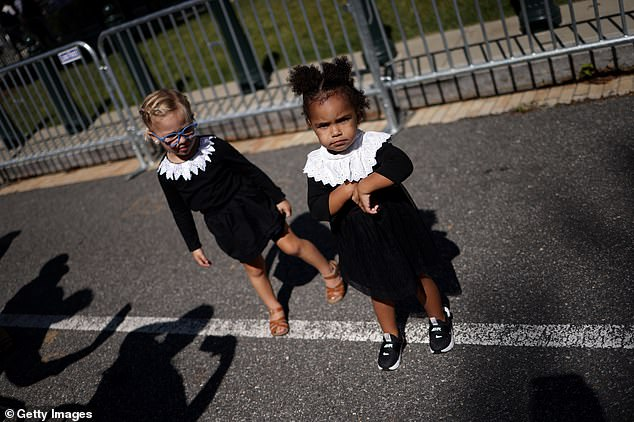 : Frankie Frezzell (R), 2, and Lucille Wilson (L), 3, wait in line dressed in tribute Ginsburg with her signature white lace collar