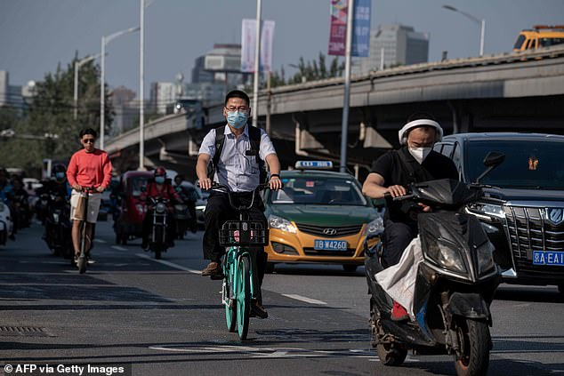 The trend for leg-extending surgery swept China where minimum heights are often quoted in personal adverts and job advertisements as the country opened up to the West. This file photo shows Chinese men commuting on a street in Beijing on September 24