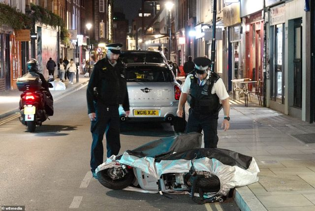 A police officer in Soho, London, bends down to pick up a motorcycle as officers prepare to help enforce the 10pm curfew