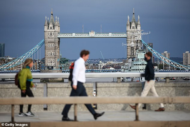 Commuters cross London Bridge on September 24 in London, England. Beginning in November when the current furlough scheme ends, the government will subsidise the pay of employees who are working fewer hours due to lower demand
