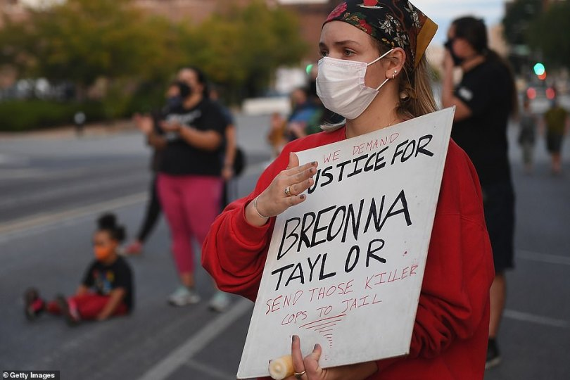 A Black Lives Matter protester in St. Louis holds a sign that reads 'We demand justice for Breonna Taylor. Send those killer cops to jail'