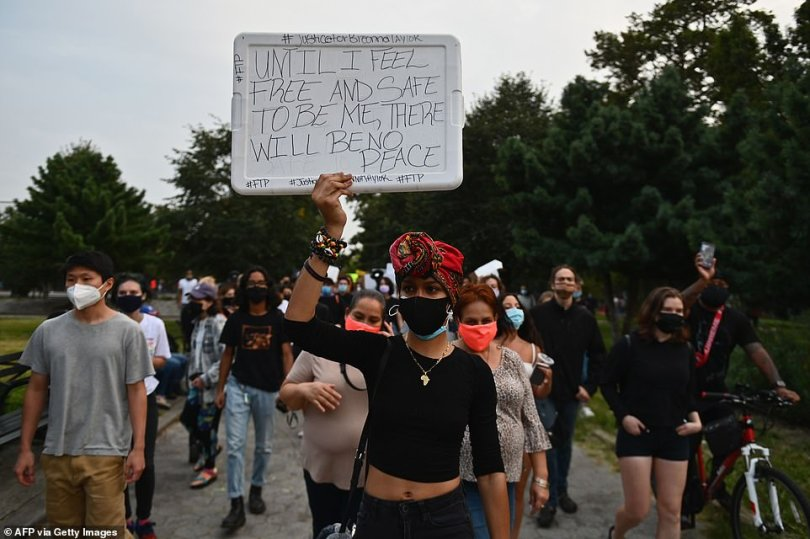 A protester in Brooklyn holds up a sign that reads: 'Until I feel free and safe to be me, there will be no peace'