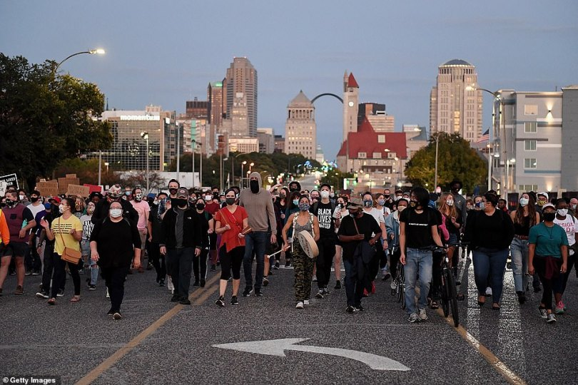 The St. Louis skyline is seen in the background as demonstrators take to the streets of the city on Thursday