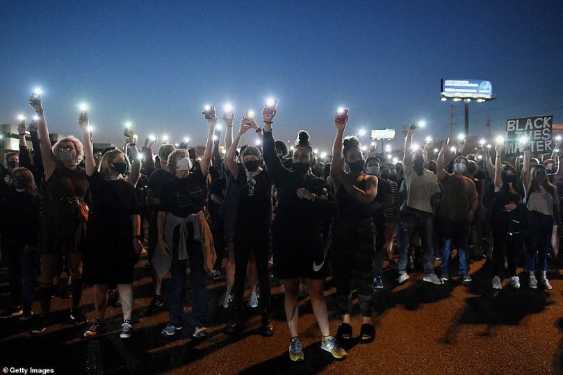 Protesters light up their cell phones during a protest action on Interstate 64 last night in St Louis, Missouri