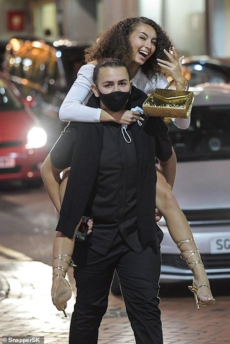 A man gives a woman a piggy-back in Birmingham city centre