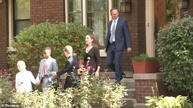 Judge Amy Coney Barrett (second from right) is photographed leaving her Indiana home Saturday followed by her husband Jesse Barrett (right) and her sons (from left) Benjamin, John Peter and Liam