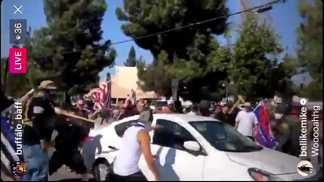 A Black Lives Matter organizer has been arrested after video showed her driving a car into a crowd of Trump supporters in southern California, injuring two