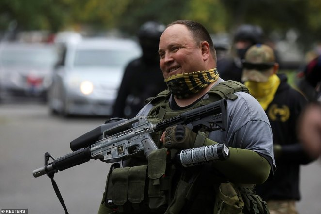 A supporter of the far right group Proud Boys carries a paintball gun at a rally in Portland, Oregon on Saturday