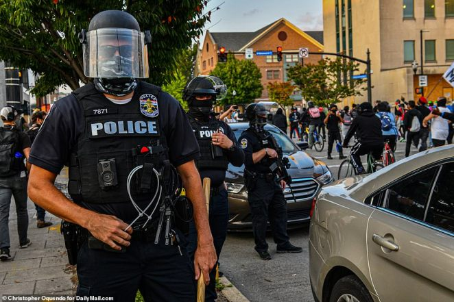 Pictured are police officers standing by as protesters march past them Saturday afternoon in Louisville