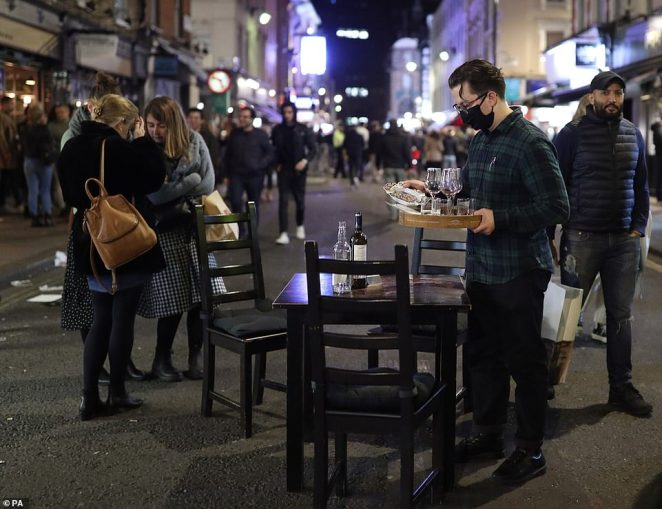 A member of bar staff clears a table in the street ahead of closing time in Soho, London, as people braved the cold to eat out