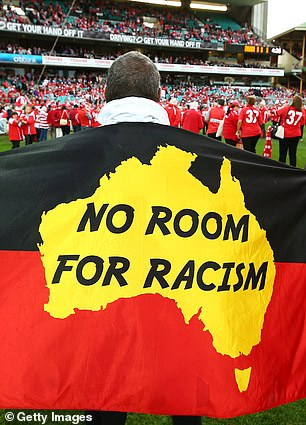 Fans display flags in support of Adam Goodes of the Sydney Swans in 2015