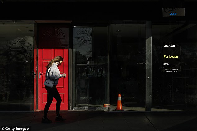 Chapel Street, Melbourne, is usually bustling. Pictured: a woman walks alone past an empty shop on the famous strip on September 6. Traders say the lockdowns are killing their business