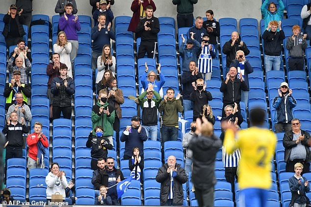 The Government has scrapped plans to bring back crowds to sports venues from October 1. Socially distanced fans are pictured taking part in a pilot during a match between Brighton and Chelsea on August 29