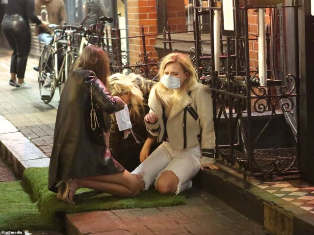 Meanwhile in Soho, in the West End of London, three women were pictured with their face coverings on the ground outside a bar