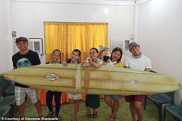 Giovanne Branzuela pictured posing with Falter's board that traveled across the ocean