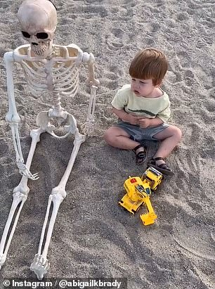 Theo is seen here playing in the sand with his skeleton friend