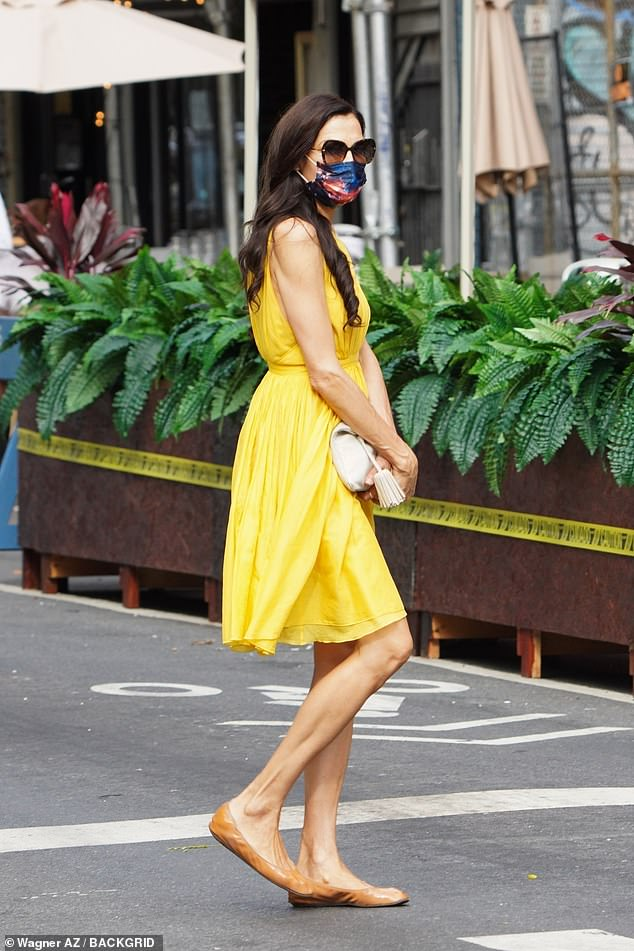 Leggy display: While flaunting her tanned and toned legs, the 55-year-old former Bond girl looked like a ray of sunshine in a flirty yellow dress and a blue galaxy mask