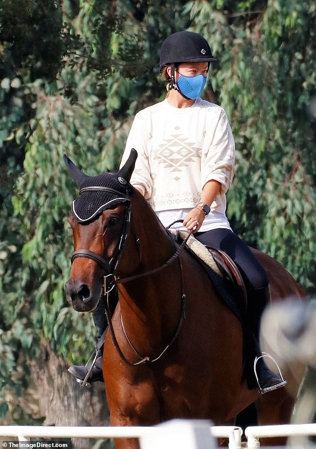 Love to ride: The actress and director, 36, wore a safety helmet over her hair that was tied back into a ponytail and had a blue face mask with her which she wore when necessary