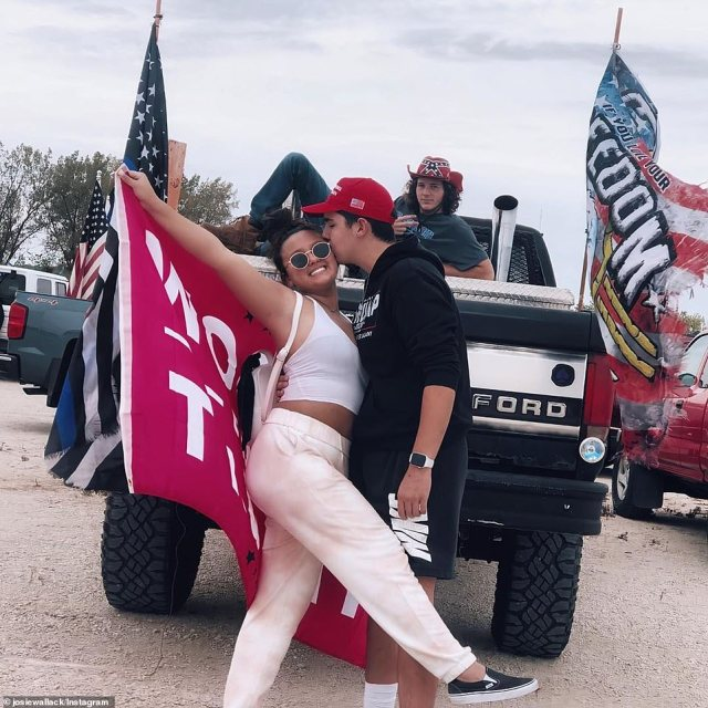 A couple kiss in front of Trump flags where a rally for Trump was preparing to be held at the Kane County Fairgrounds in St. Charles
